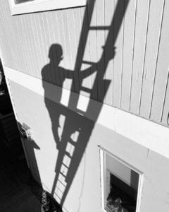 Shadow climbing up a ladder